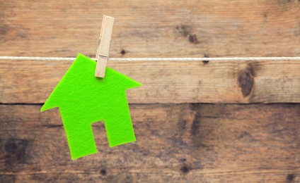 Green eco house attach to rope with clothes pins on wooden background